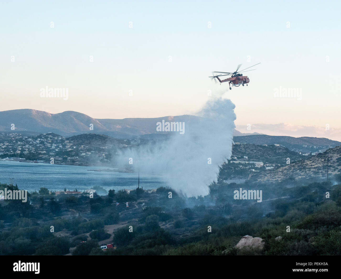 Fire emergency services helicopter spraying water preventing the fire from spreading further on the mountains. Saronida, East Attica, Greece, Europe. Stock Photo