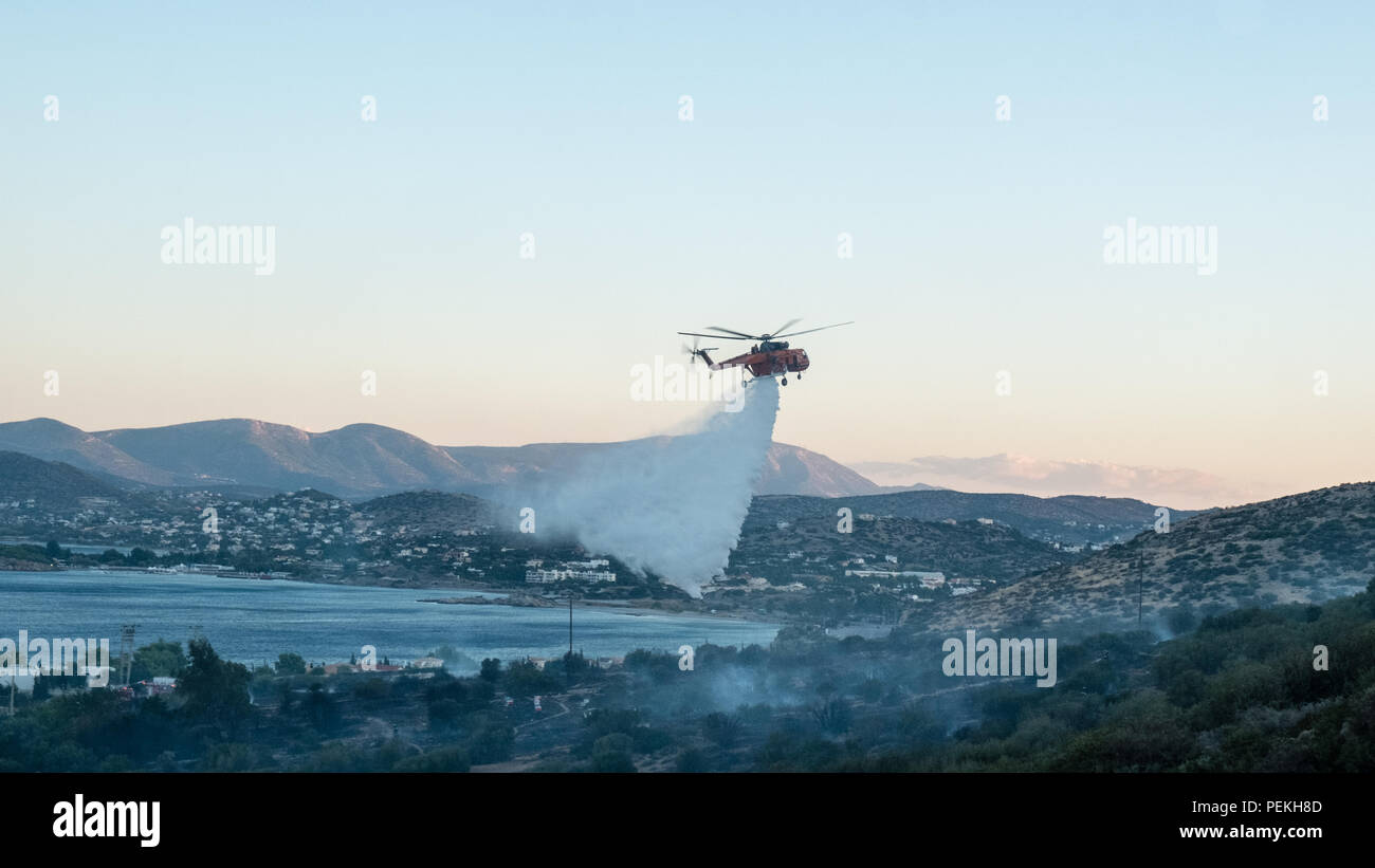 Fire emergency services spraying water preventing the fire from spreading further on the mountains. Saronida, East Attica, Greece, Europe. Stock Photo