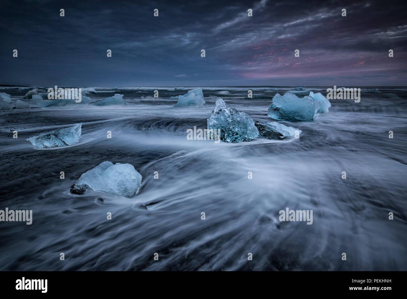 Glacial Ice washed ashore on the beach at Jokulsarlon Black Sand Beach also known as Breidamerkursandur, Iceland - Stock Image