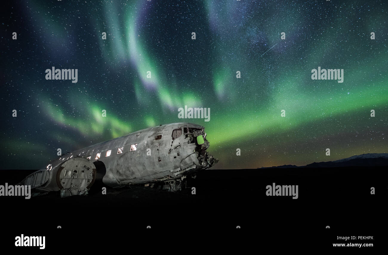 The crashed DC-3 Plane wreck with Northern Lights & Aurora Borealis at Solheimasandur, Iceland Stock Photo