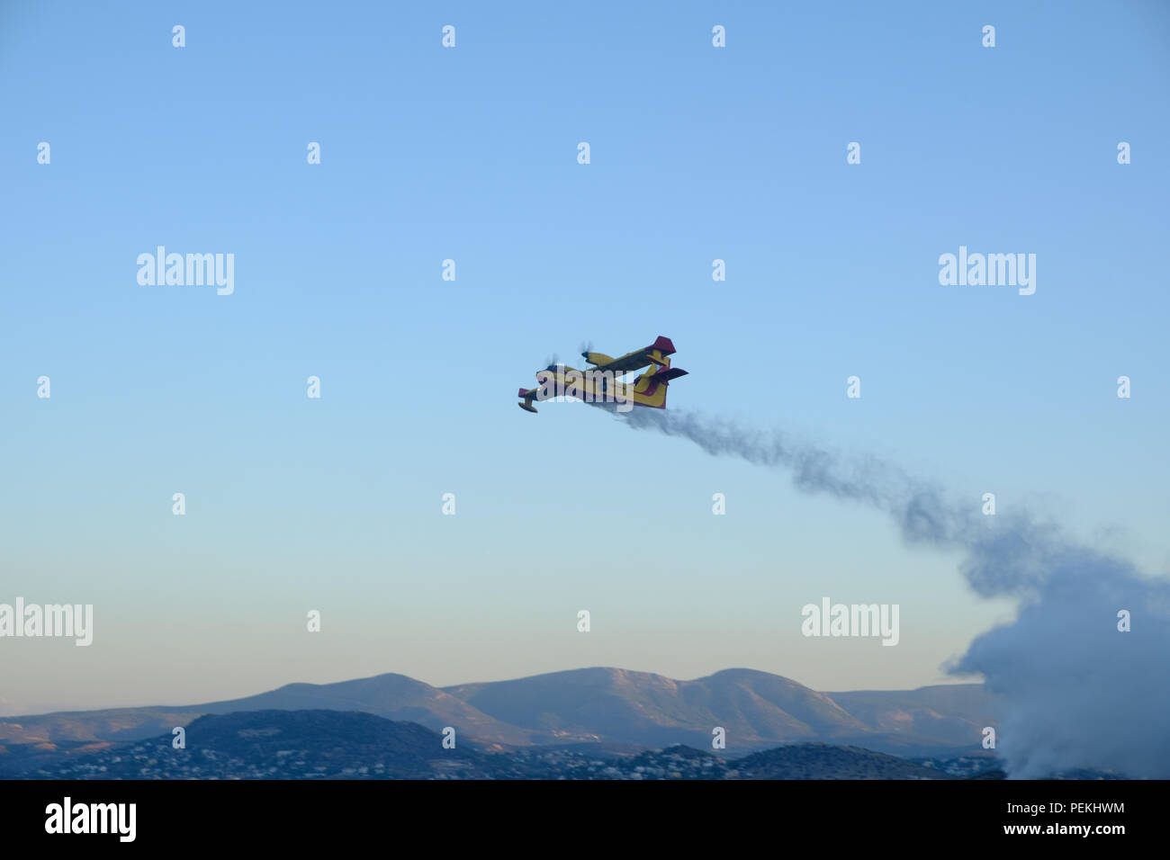 Emergency fire service aeroplane spraying water preventing the fire from spreading further on the mountains of Saronida, East Attica, Greece, Europe. Stock Photo