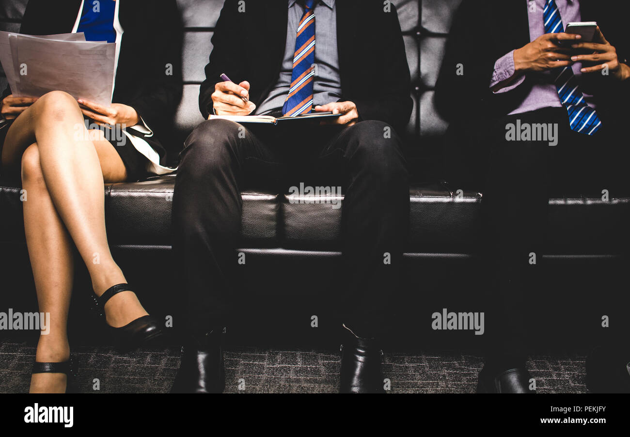 stressful people group sitting and waiting to interview for a job on sofa. - Stock Image