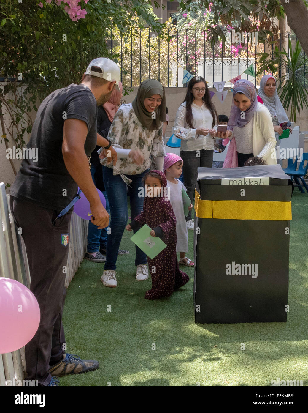 Cairo, Egypt. Children at  pre-school celebrating the forthcoming eid (holiday) by walking around an imitation Meccan kaaba. - Stock Image