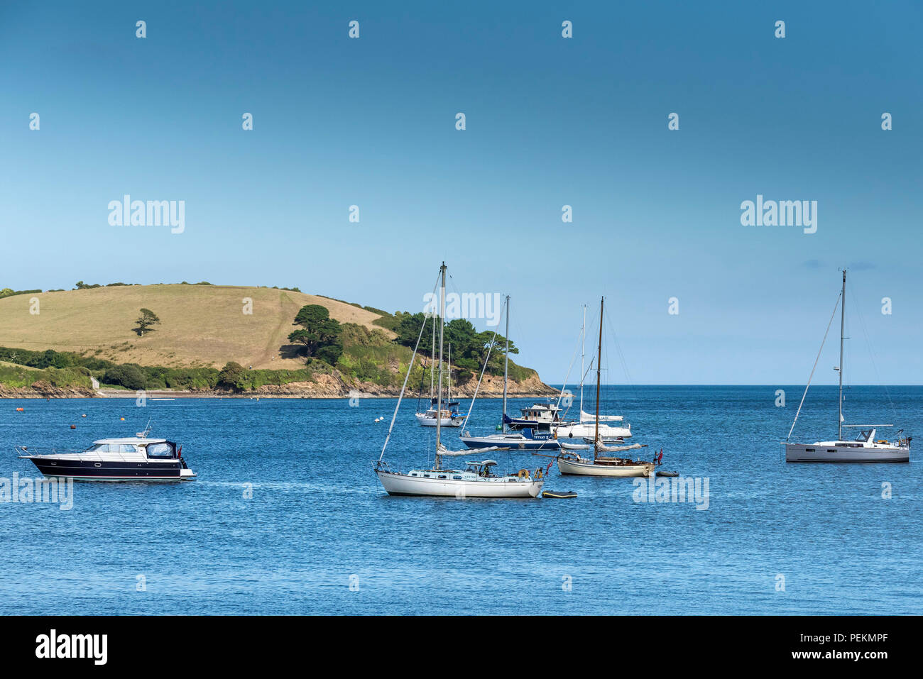 Sail boats yachts motor boats crusiers moored in Polgwidden Cove on the Helford River in Cornwall. - Stock Image