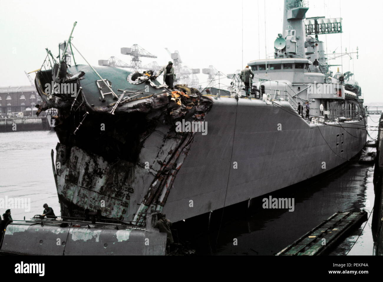 AJAXNETPHOTO.  13TH NOVEMBER, 1975. PORTSMOUTH, ENGLAND. - CRUNCH! - PICTURED ALONGSIDE AT THE NAVAL BASE DOCKYARD WITH 14 FEET OF HER BOW SMASHED; THE GP LEANDER CLASS FRIGATE HMS ACHILLES (2500 TONS). THE FRIGATE COLLIDED WITH LIBERIAN OIL TANKER OLYMPIC ALLIANCE 1 MILES S.E. OF DOVER NEAR VARNE LIGHTSHIP ON NIGHT OF 12/13 NOV 1975. THREE CREWMEN ON ACHILLES WERE INJURED. PHOTO:JONATHAN EASTLAND/AJAX REF:401279_1 Stock Photo