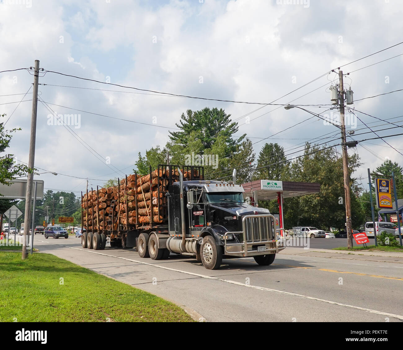 A loaded Kenworth semi-truck hauling logs through Speculator, NY USA - Stock Image