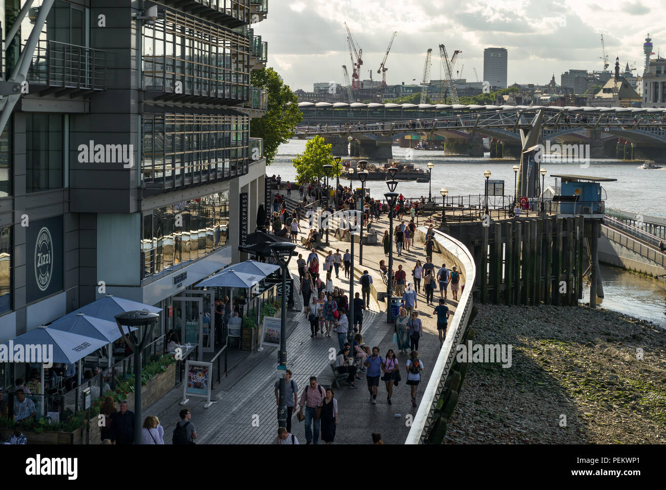 Riverside House building with Zizzi restaurant, people walking along Bankside with the river Thames and Millennium Bridge in background, London, UK Stock Photo