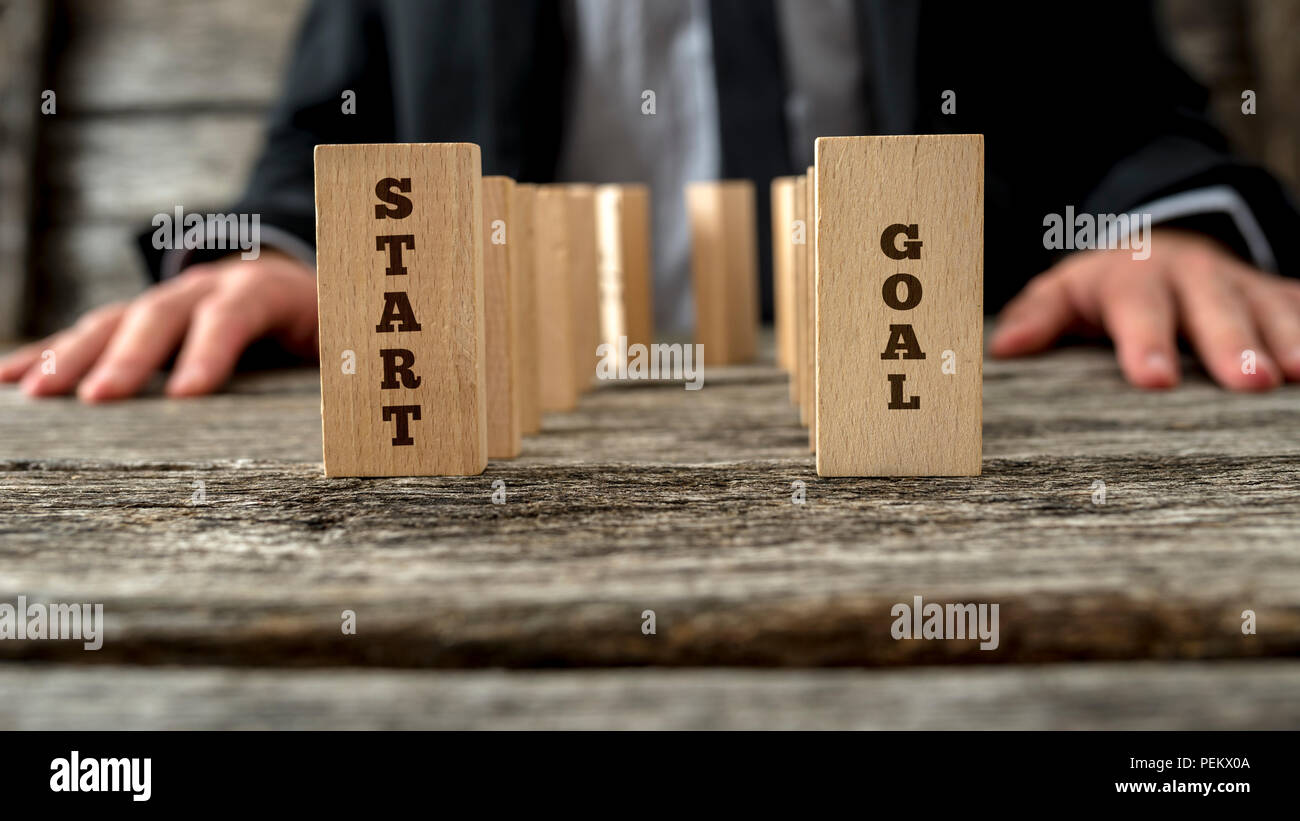 Wooden dominoes on old table with text start and goal, body of businessman on background. - Stock Image
