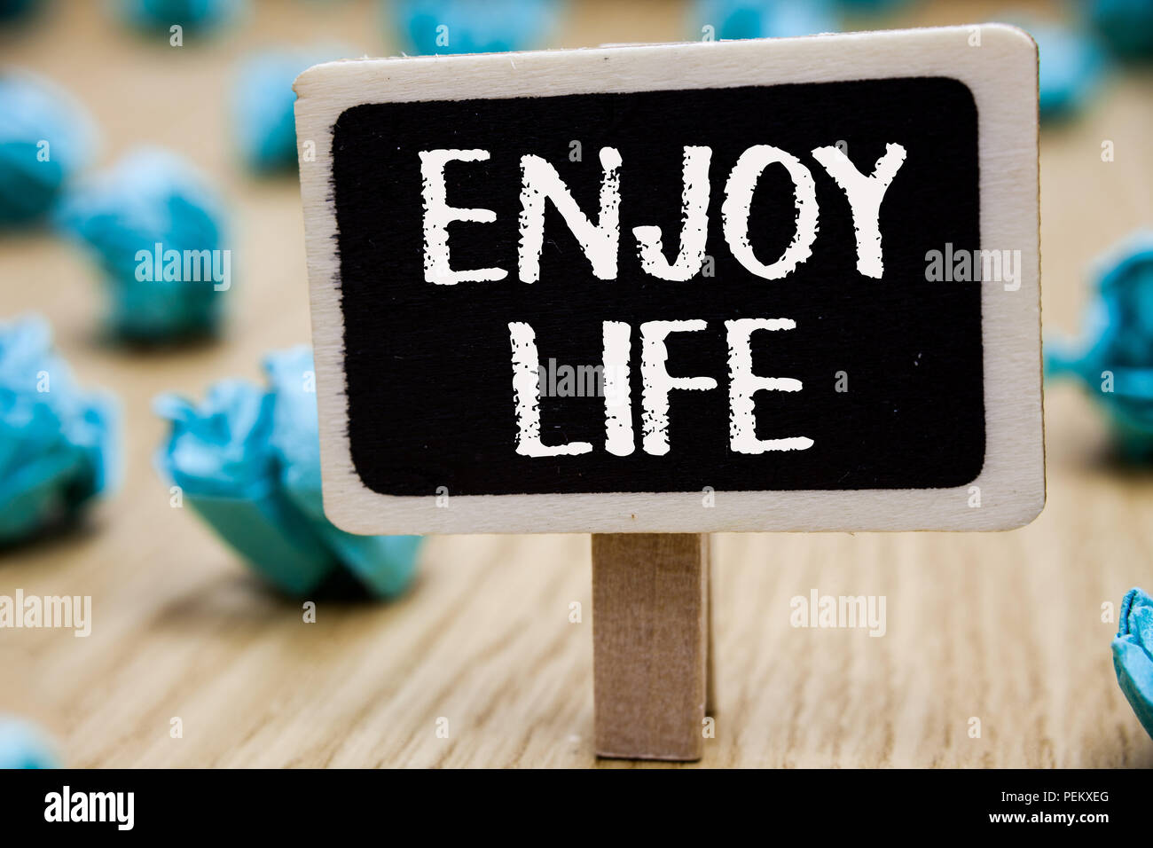 Text sign showing Enjoy Life. Conceptual photo Any thing, place,food or person, that makes you relax and happy Blackboard crumpled papers several trie - Stock Image