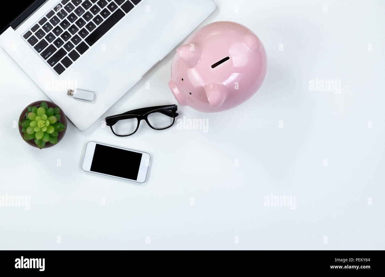 Top view white desktop with saving piggy bank and technology plus copy space - Stock Image