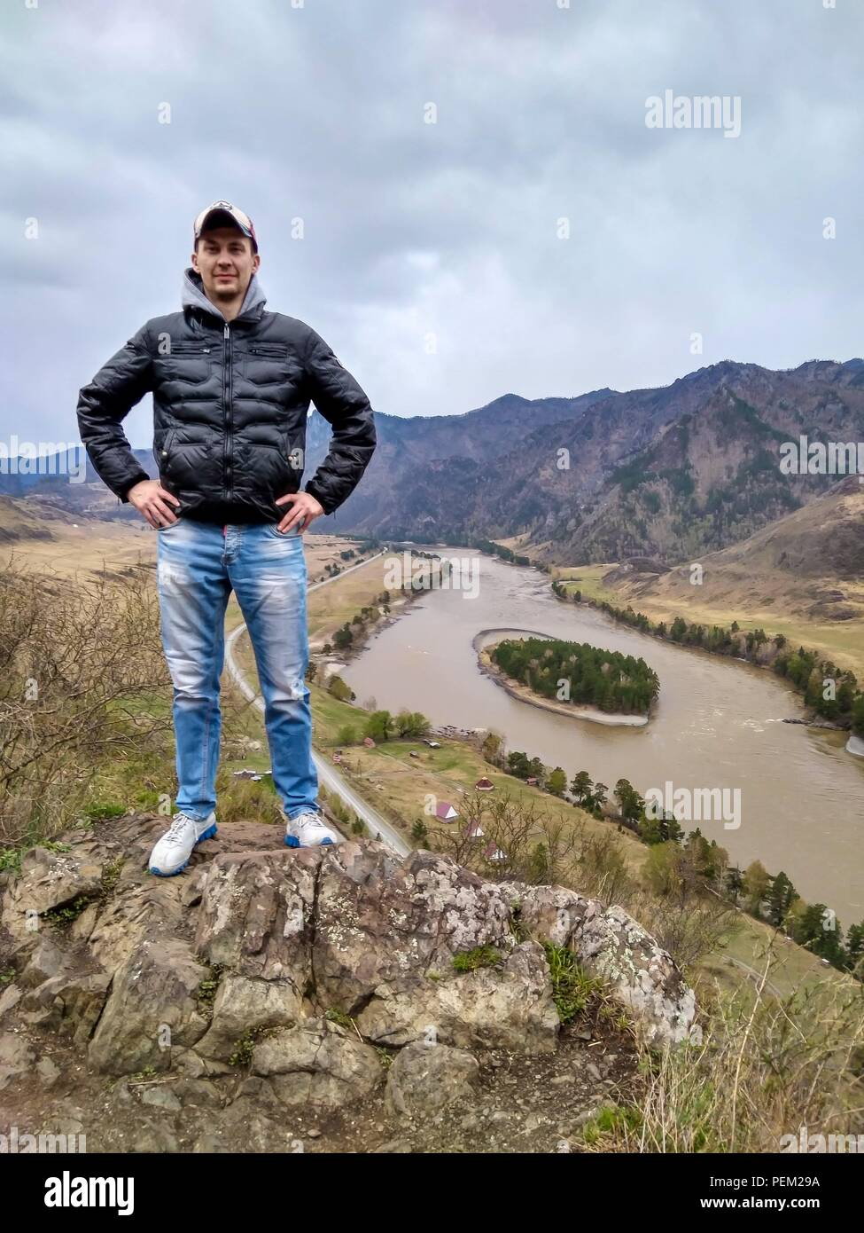 Young man in the cap is standing on the edge of a cliff in Altai Mountains and looks at the. Katun river near the road under him. Stock Photo