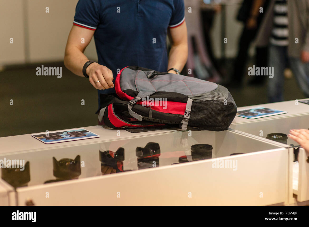RIGA. LATVIA.  - MAY 11, 2018: The man puts the equipment bought in the photo store in the backpack. - Stock Image