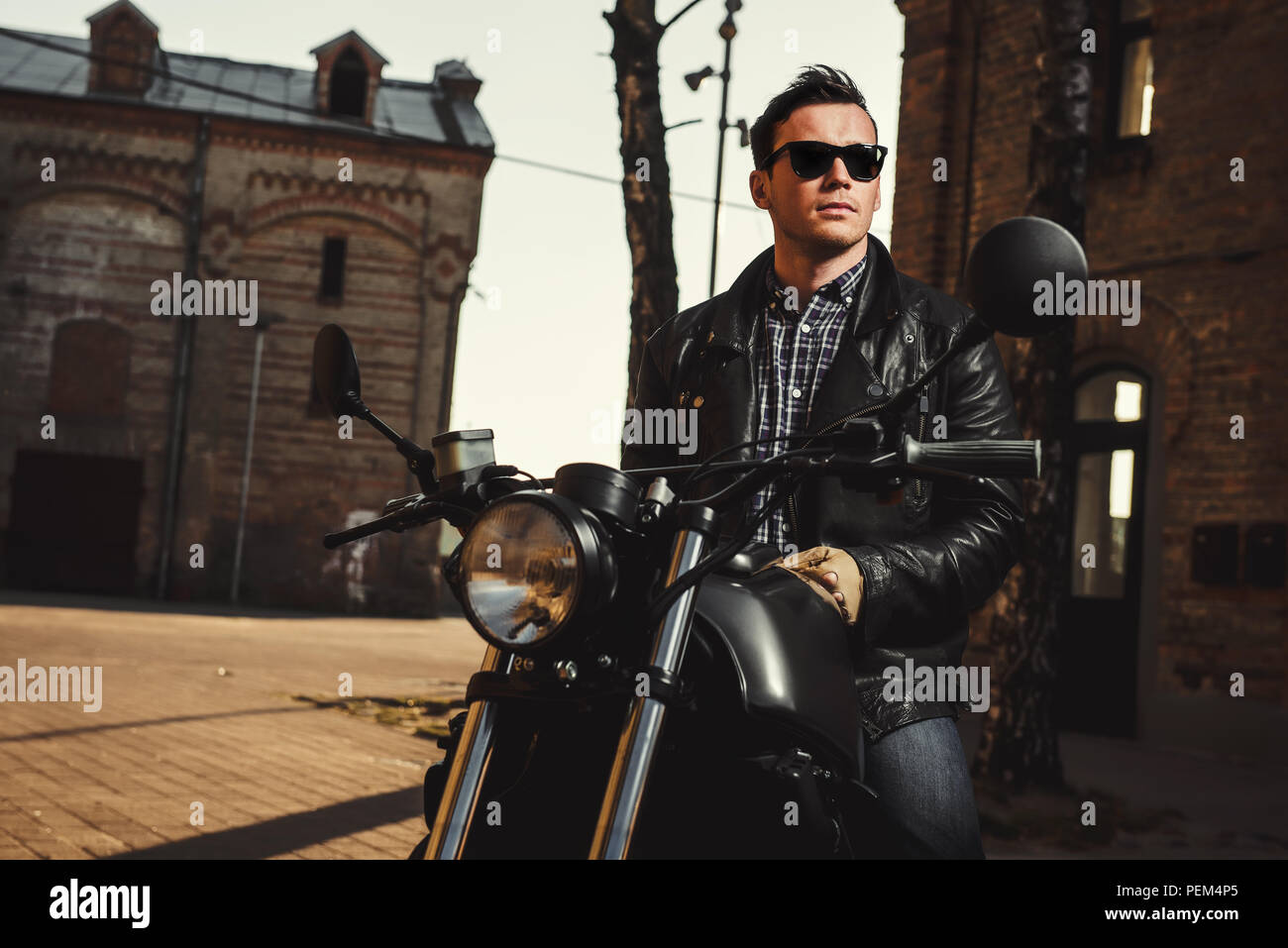 Man sitting on a cafe-racer motorcycle outdoors - Stock Image