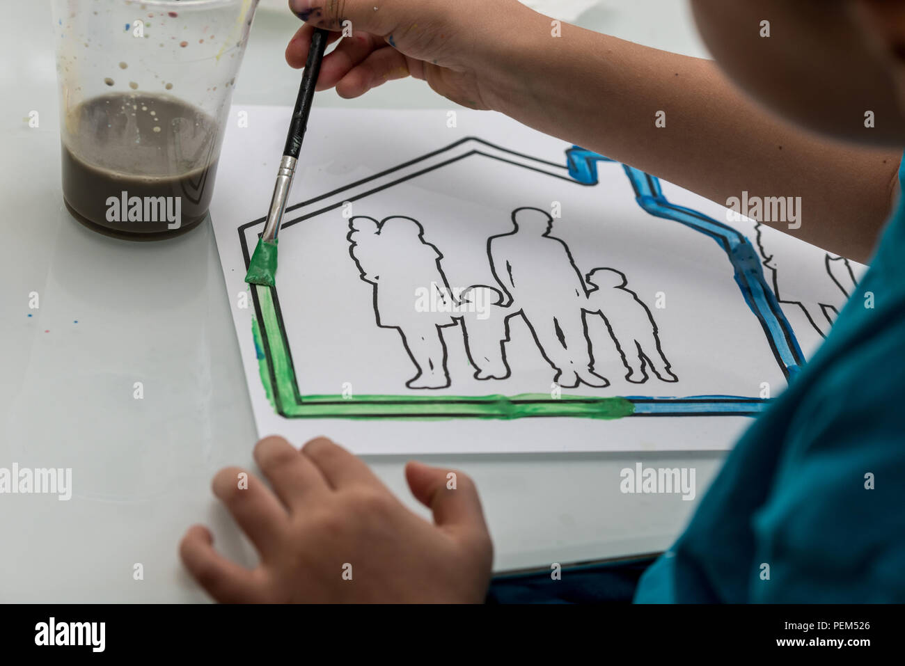 Young child colouring in a sketch of a family in a house using a paintbrush and watercolour paints in an over the shoulder view of the artwork. - Stock Image