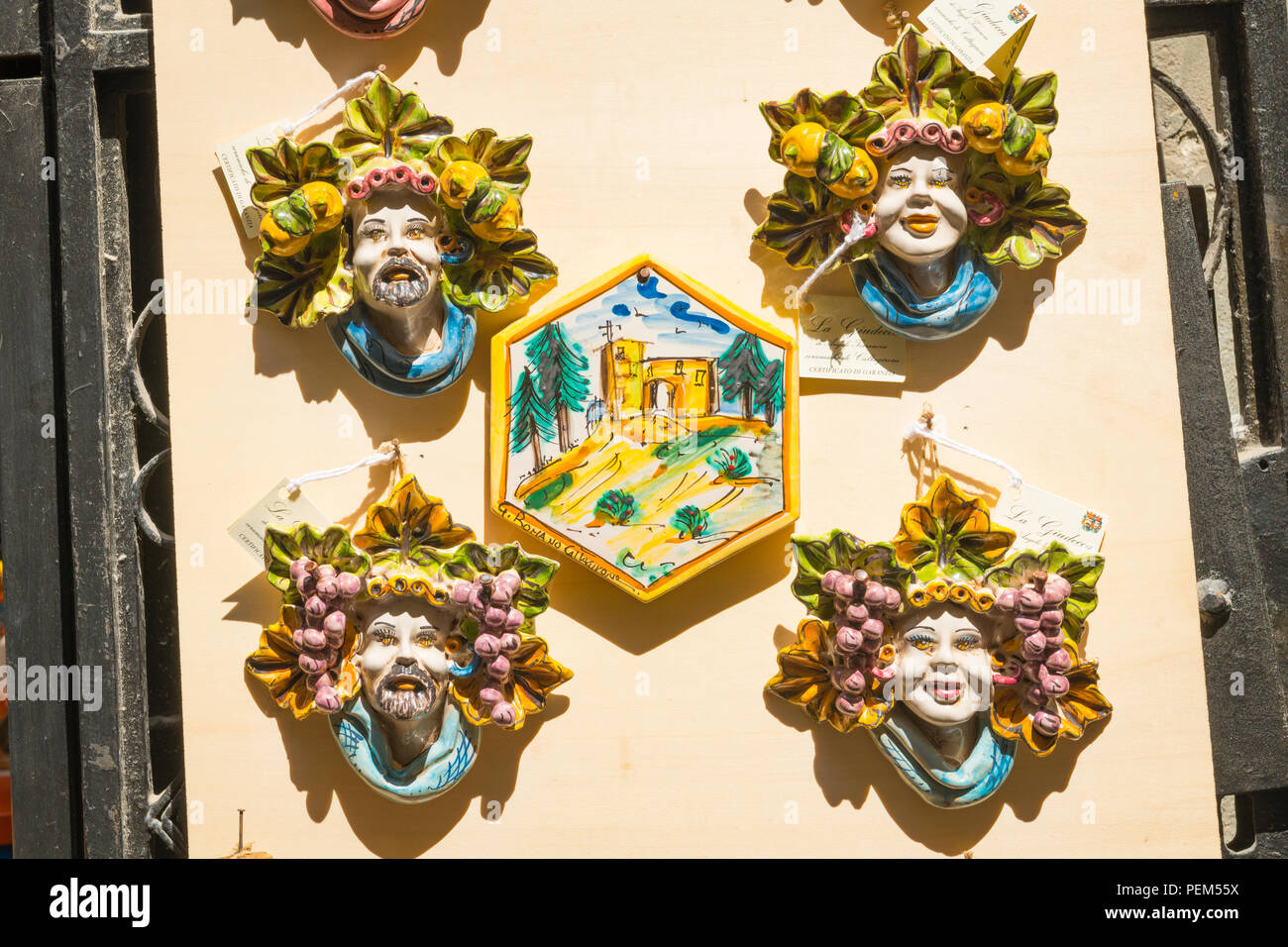 Italy Sicily Syracuse Siracusa Ortygia souvenir shop store typical pottery ceramic smiling faces surrounded by fruit painted scene display board - Stock Image