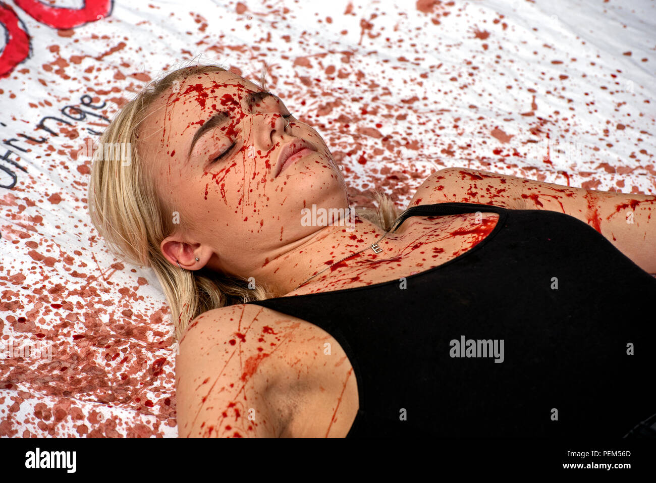 A cast member from University of York Drama Society, splattered with fake blood, promoting 'Bad Dog' on the High Street during the Edinburgh   Fringe. - Stock Image