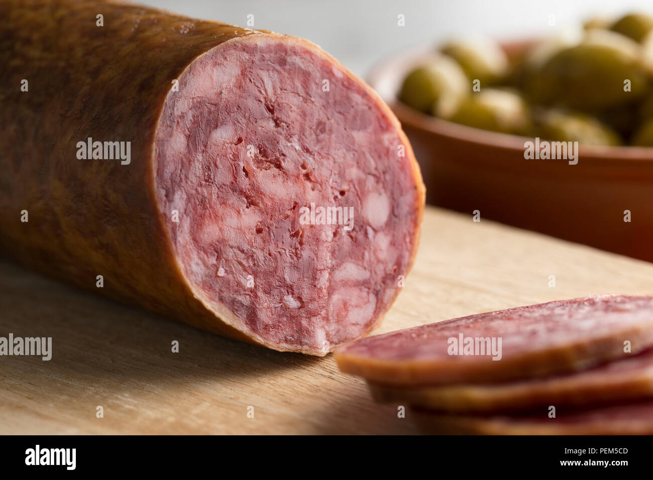Traditional piece of Spanish Salchichon sausage and slices close up - Stock Image