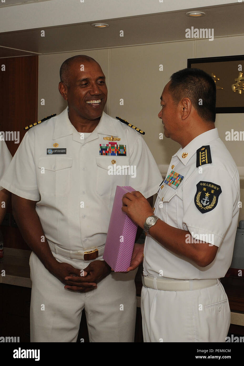 151213-N-ZK021-010   PEARL HARBOR (Dec. 13, 2015) Senior Captain Wang Jianxum, deputy chief of staff of East Sea Fleet, People's Liberation Army (Navy) and commander, Escort Task Group, CNS Jinan (DDG-152) presents a gift to Capt. Stanley Keeve, commander, Joint Base Pearl Harbor-Hickam during a visit aboard CNS Jinan (DDG-152). The port visit demonstrates parity and reciprocity between two maritime nations. As part of a planned series of military-to-military exchanges between two nations, Chinese and U.S. naval officers will conduct dialogues to build confidence and mutual understanding. Duri - Stock Image