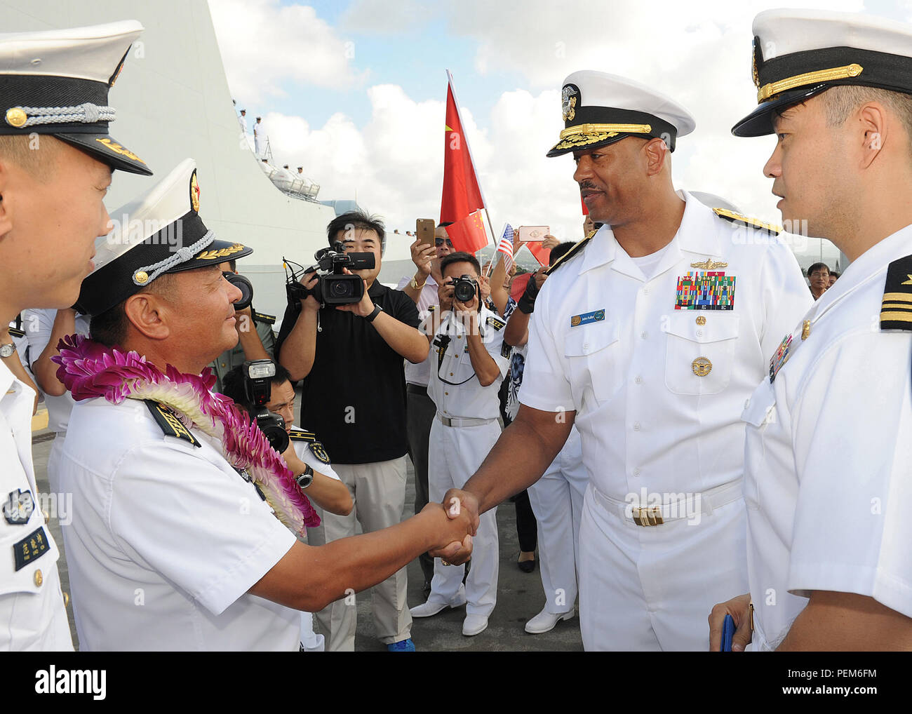 151213-N-ZK021-004    PEARL HARBOR (Dec. 13, 2015) Rear Adm. John Fuller, commander, Navy Region Hawaii and Naval Surface Group Middle Pacific greets Senior Captain Wang Jianxum, deputy chief of staff of East Sea Fleet, People's Liberation Army (Navy) and commander, Escort Task Group, CNS Jinan (DDG-152), during a routine port visit to Hawaii. The port visit demonstrates parity and reciprocity between two maritime nations. As part of a planned series of military-to-military exchanges between two nations, Chinese and U.S. naval officers will conduct dialogues to build confidence and mutual unde - Stock Image