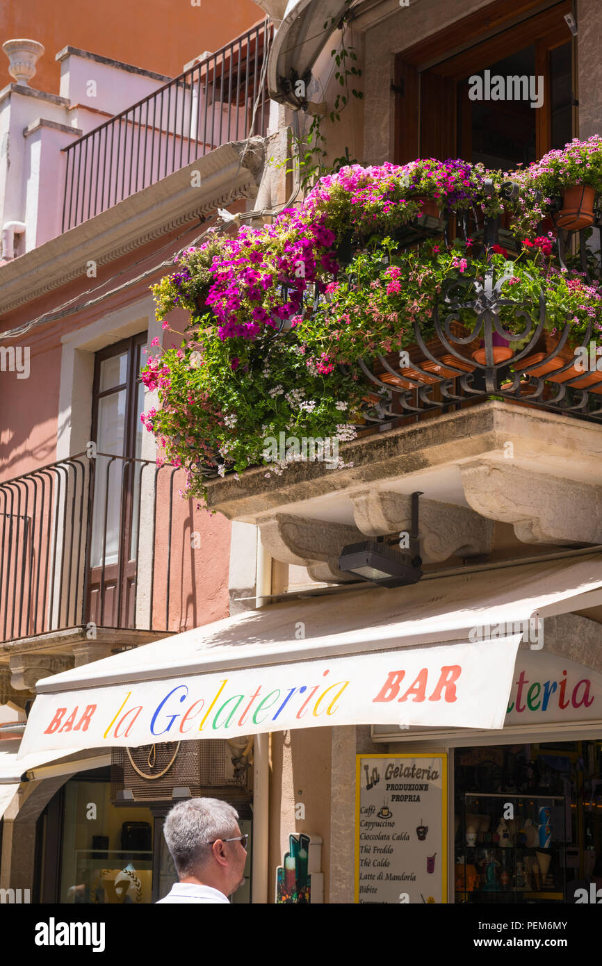 Italy Sicily Monte Tauro most famous luxury tourist resort Taormina bar La Gelateria shop store cafe canopy blind ice-cream balcony flowers Stock Photo
