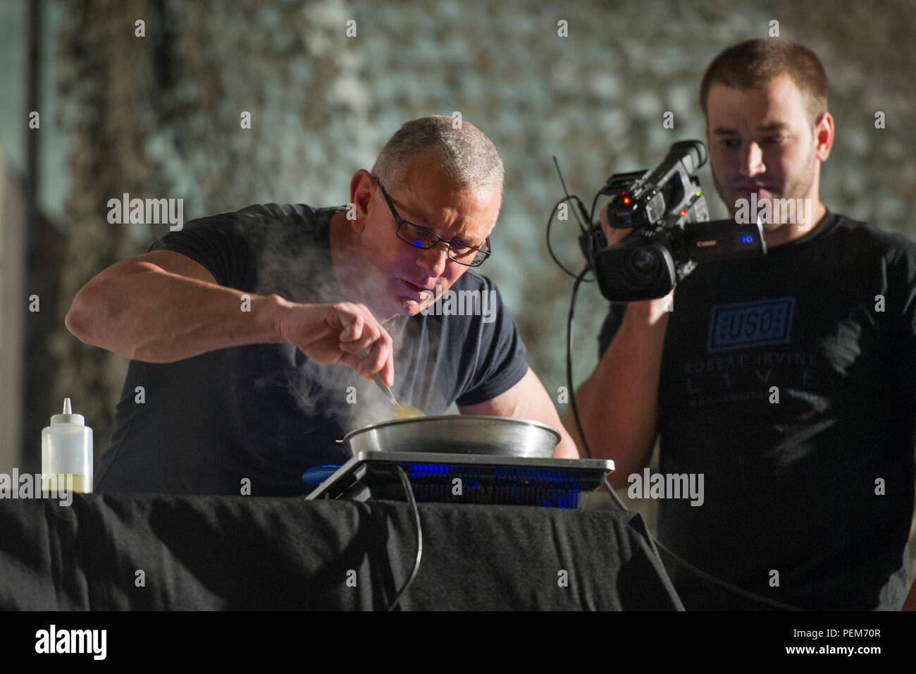Chef Robert Irvine prepares a meal during a USO show at