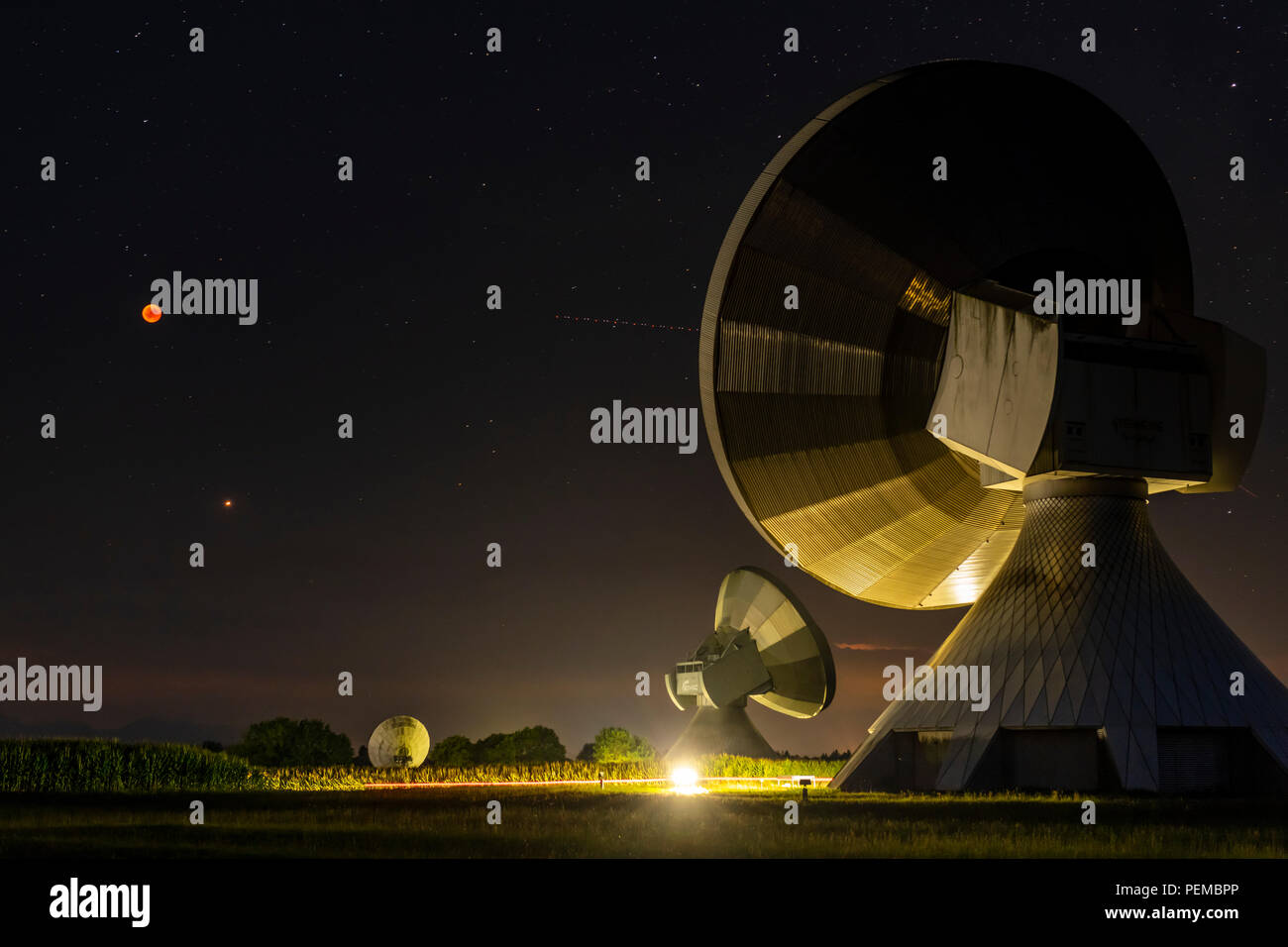 Parabolic antennas with blood moon at lunar eclipse, night shot, Raisting, Upper Bavaria, Germany - Stock Image
