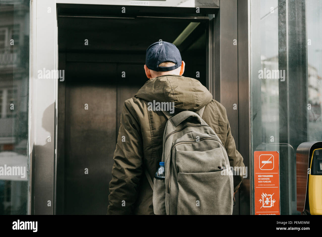 A tourist man with a backpack uses a street elevator in Porto in Portugal to go down to the metro. - Stock Image