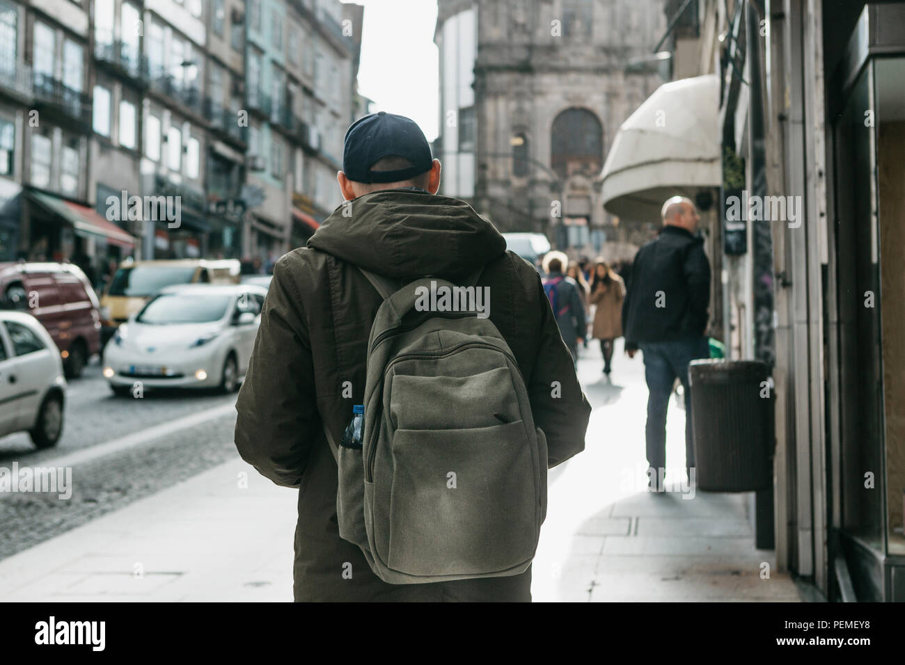 A tourist with a backpack walks down the street in Porto in Portugal. Travel around Portugal. - Stock Image