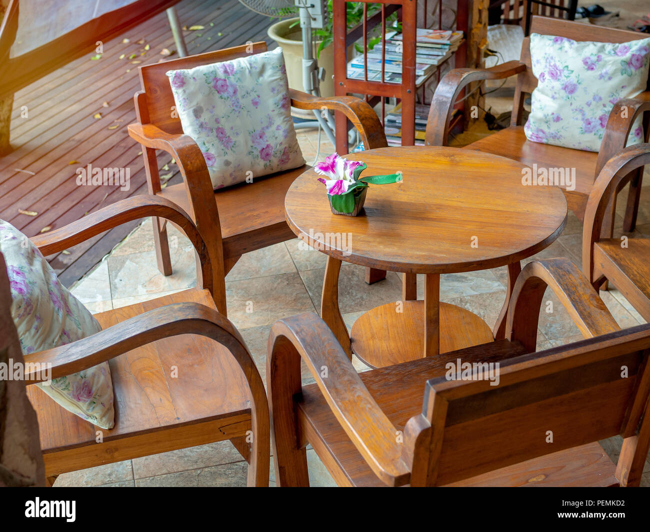 Wooden Armchairs With Pillows Round Table Flower In Pot On And Bookshelf Plank Floor Cafe