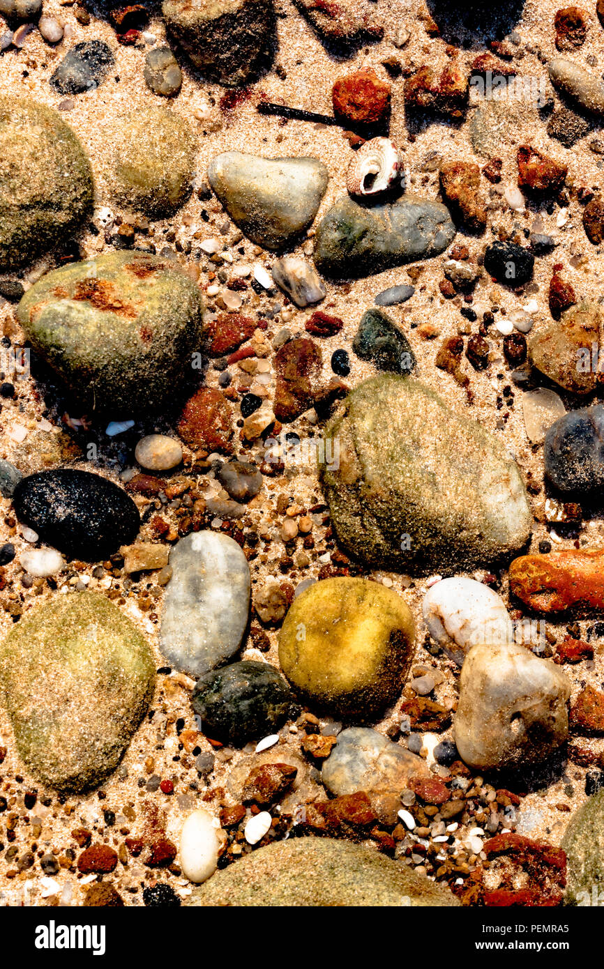 Beautiful colorful stones, sea shells and geological rocks containing minerals of sea lying underwater on the sea floor in the shallow waters. Stock Photo