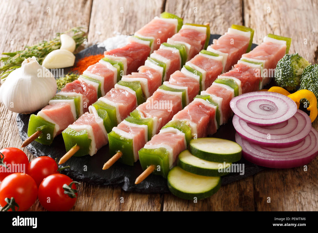 For barbecue raw shish kebab with pepper and lard on skewers close-up and ingredients, vegetables, spices, herbs on the table. horizontal Stock Photo