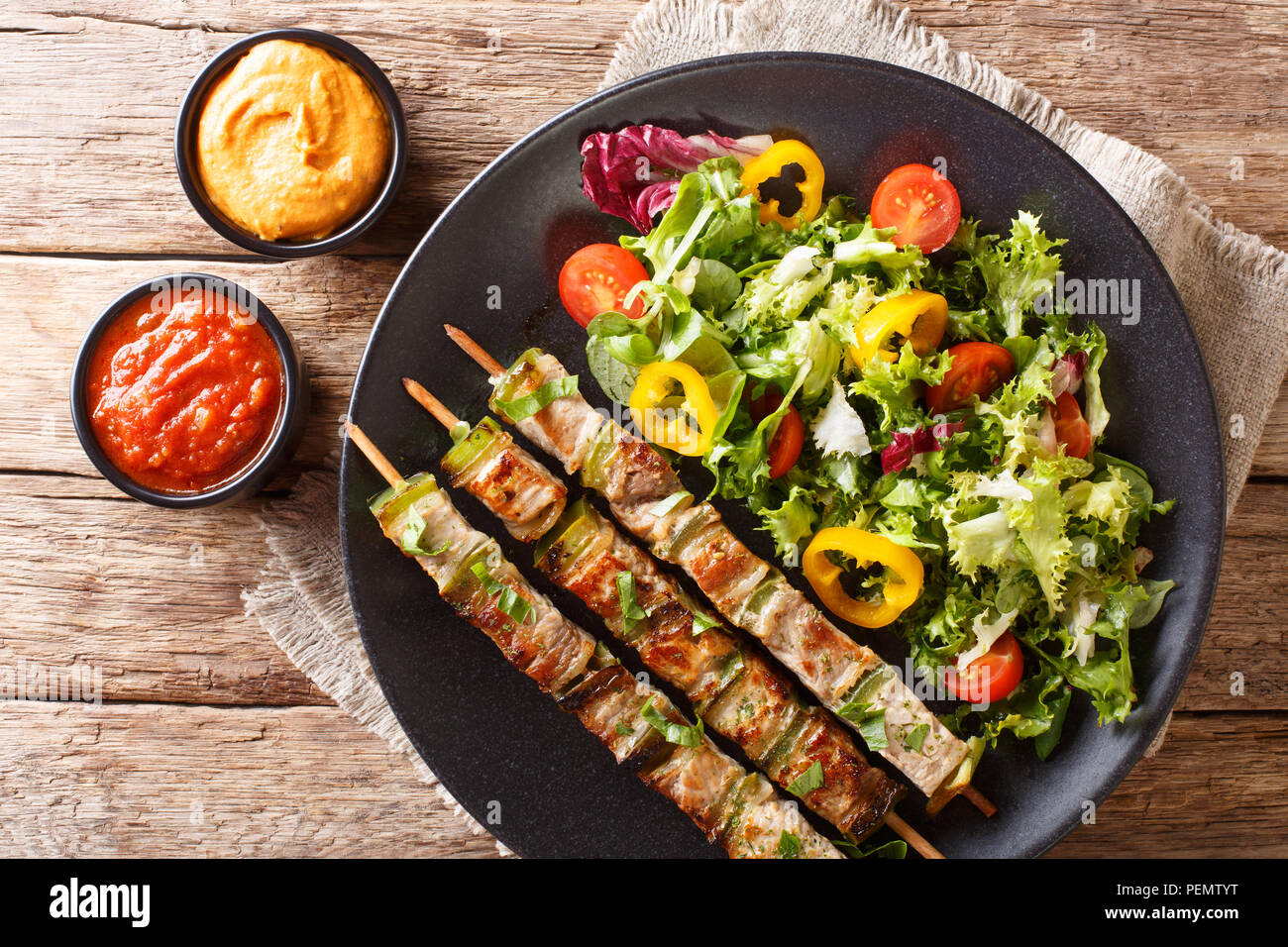 Delicious kebab on skewers with fresh vegetable salad on a plate and sauce close-up on the table. Horizontal top view from above - Stock Image