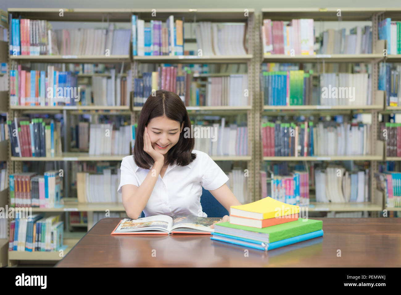 Asian student reading book in library at university. - Stock Image