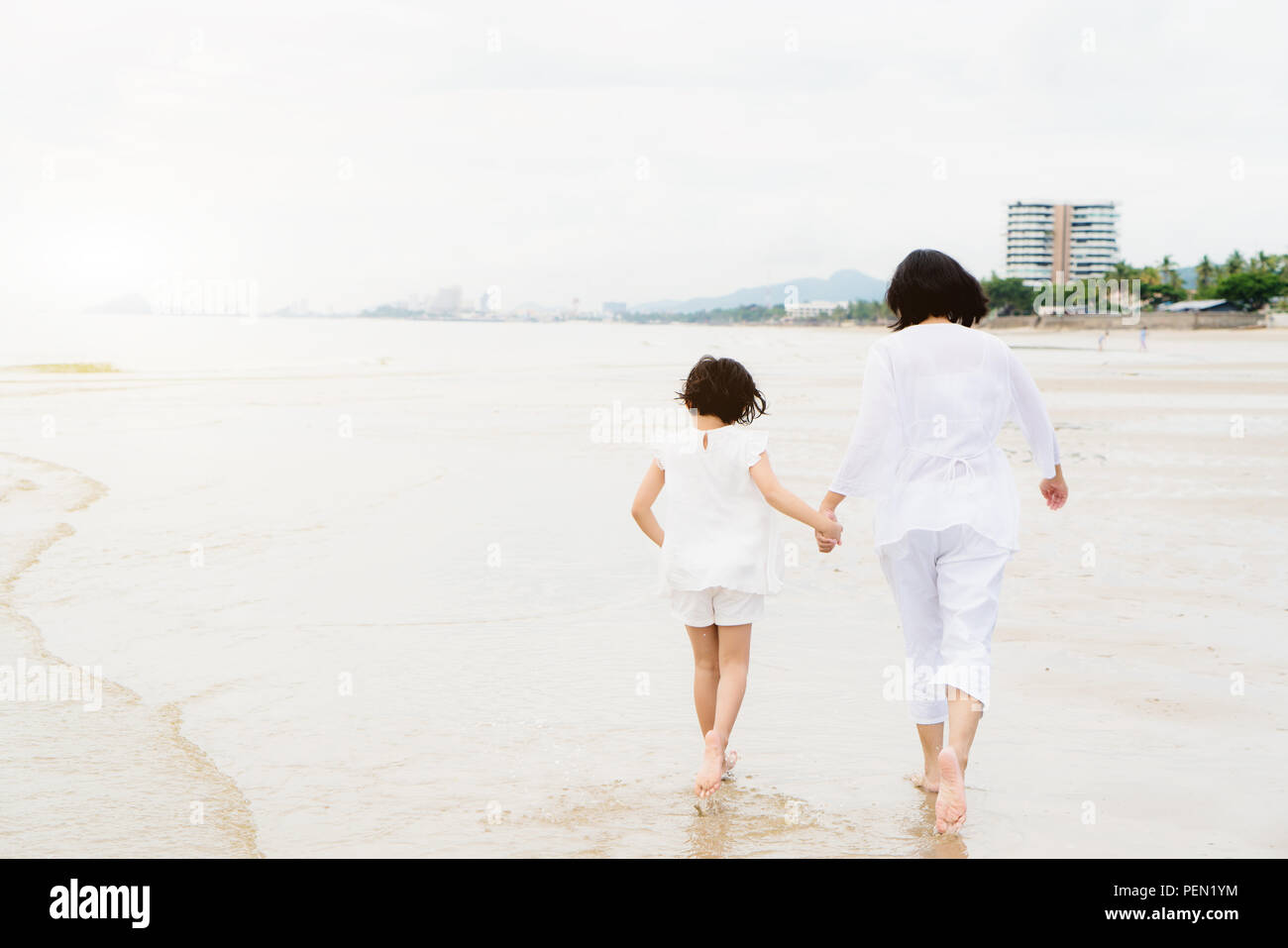 Happy Asian family mother and child daughter run, laugh and