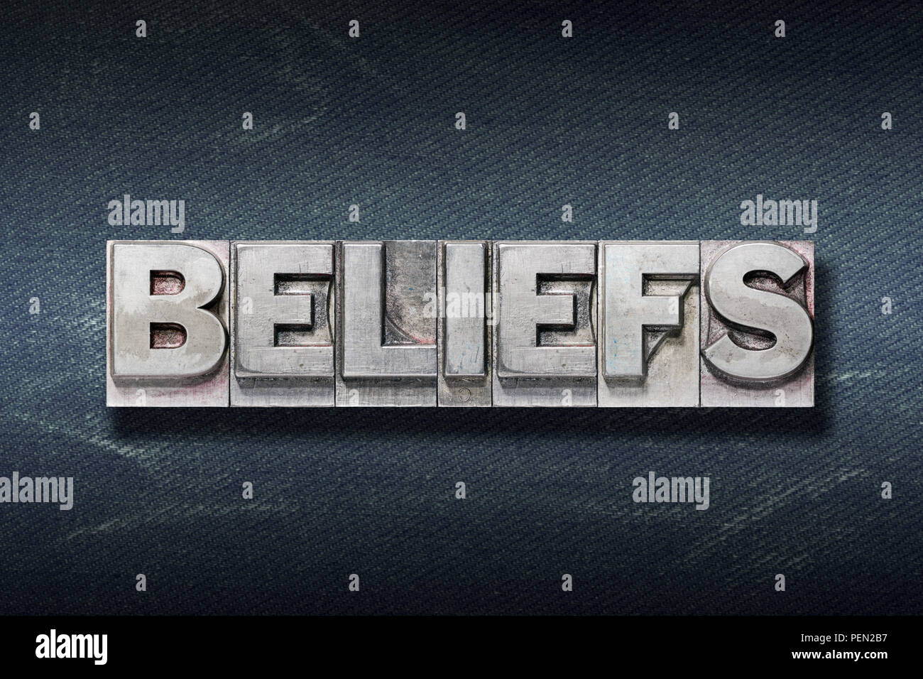 beliefs word made from metallic letterpress on dark jeans background - Stock Image