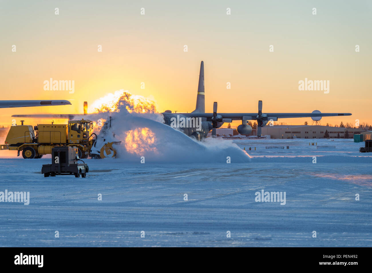 Snow plows remove snow in front of a C-130H Hercules aircraft assigned to the 153rd Airlift Wing, Wyoming Air National Guard, Dec. 16, 2015, in Cheyenne, Wyo. The National Weather Service reported a daily maximum snowfall record for Dec. 15 at Cheyenne Regional Airport with 6.7 inches of snowfall, which breaks the old record of 3.3 inches set in 1892. (U.S. Air National Guard photo by Master Sgt. Charles Delano/released) Stock Photo