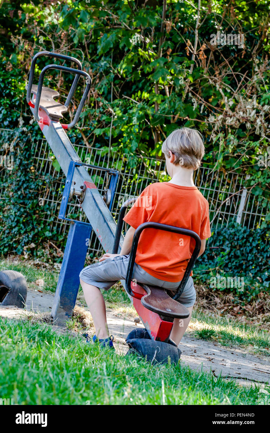 Boy alone playing at the see-saw in the playground. - Stock Image