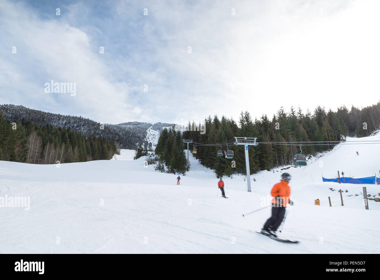 Blurred skiers going downhill on Whistler Mountain. - Stock Image