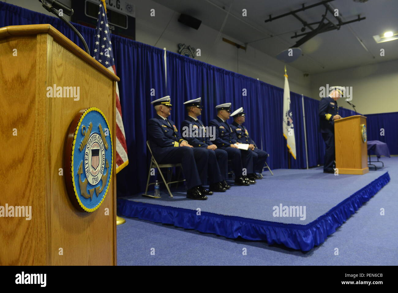 Rear Adm. Richard Gromlich, commander, Coast Guard 13th District, addresses attendees during a change-of-watch ceremony at Coast Guard Base Seattle Dec. 18, 2015. During the ceremony, Master Chief Petty Officer Charles Lindsey transferred authority as command master chief of the Coast Guard 13th District to Master Chief Petty Officer Sean McPhilamy, who reported from his prior position as command master chief of Coast Guard Base Kodiak, Alaska. (U.S. Coast Guard photo by Seaman Sarah Wilson) - Stock Image