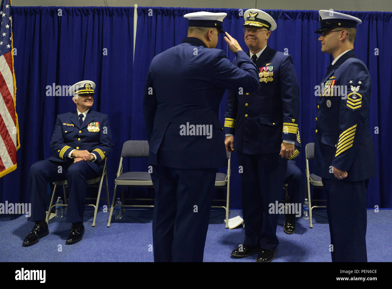 Master Chief Petty Officer Charles Lindsey, former command master chief for the Coast Guard 13th District, salutes Rear Adm. Richard Gromlich, commander, Coast Guard 13th District, as Lindsey transfers command authority to Master Chief Petty Officer Sean McPhilamy at a change-of-watch ceremony at Coast Guard Base Seattle Dec. 18, 2015. As the command master chief, McPhilamy will serve as the senior enlisted advisor to the 13th District commander for all Coast Guard missions in the Pacific Northwest region of Washington, Oregon, Idaho and Montana. (U.S. Coast Guard photo by Seaman Sarah Wilson) - Stock Image