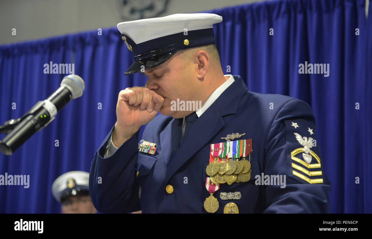 Master Chief Petty Officer Charles Lindsey, former command master chief for the Coast Guard 13th District, holds back tears as he reflects on his 23-year-long Coast Guard career during a change-of-watch and retirement ceremony at Coast Guard Base Seattle Dec. 18, 2015. Lindsey is retiring to Florida with his wife, Leslie, and their two sons Keygan and Bosun. (U.S. Coast Guard photo by Seaman Sarah Wilson) - Stock Image