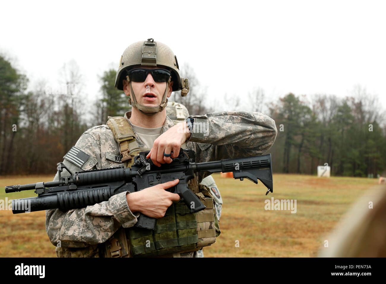 U.S. Army Staff Sgt. Brian Kohl, assigned to 55th Signal Company (Combat Camera), demonstrates the function of a quadrant sight on a M203 grenade launcher during heavy weapons training at Fort A.P. Hill, Va., Dec. 1, 2015. The 55th Signal Company conducted heavy weapons training to familiarize with the basic operations and functions of the heavy weapon system. (U.S. Army photo by Spc. Darnell Torres/Released). - Stock Image