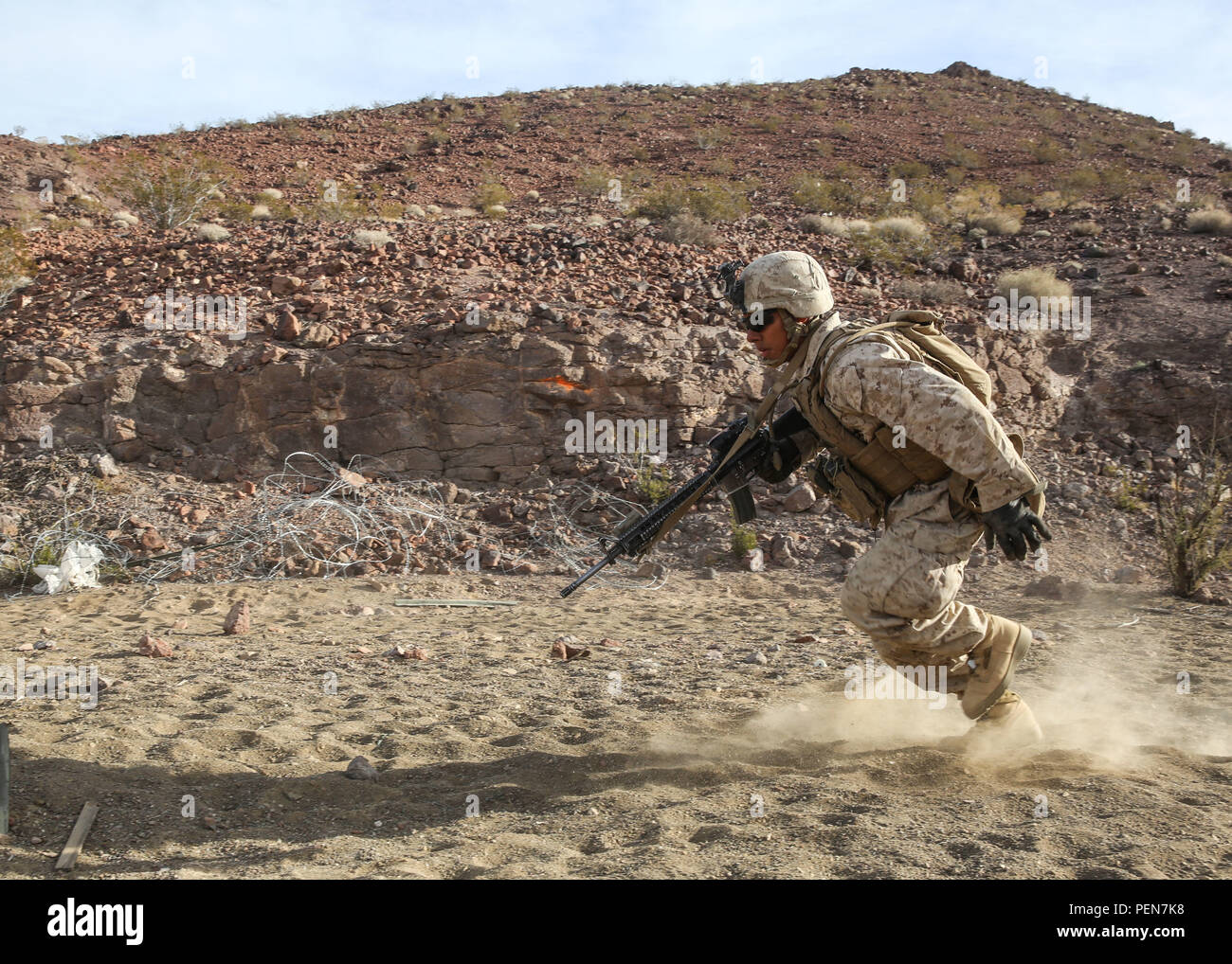 A Marine darts for cover during a company supported, live-fire assault during a Marine Corps Combat Readiness Evaluation at Marine Corps Air Ground Combat Center Twentynine Palms, Calif., Dec. 7, 2015. The purpose of a MCCRE is to evaluate Marines' collective performance in specific mission requirements that will prepare them for their upcoming deployment rotation.The Marine is with 2nd Battalion, 7th Marine Regiment, 1st Marine Division. (U.S. Marine Corps photo by Lance Cpl. Devan K. Gowans) - Stock Image