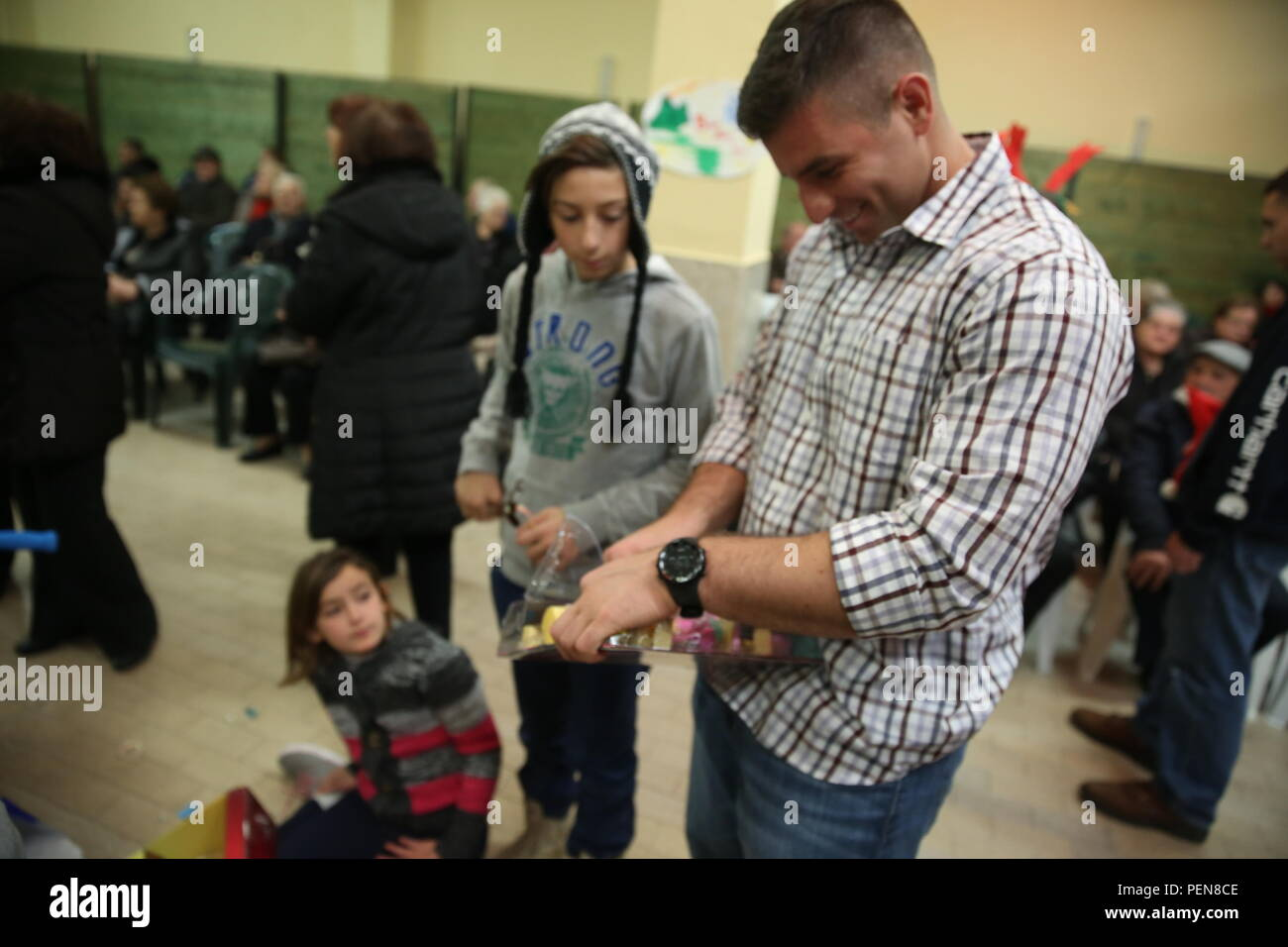 Staff Sgt. Ryan Nikzad opens a gift for a girl during a Christmas party at the Giovanna Romeo Orphanage, Dec. 22, in Belpasso, Italy. More than 30 Marines and sailors with Special-Purpose Marine Air-Ground Task Force Crisis Response-Africa, participated in the event, where they also donated food and toys to the orphanage, sang Christmas carols and interacted with the children. Stock Photo