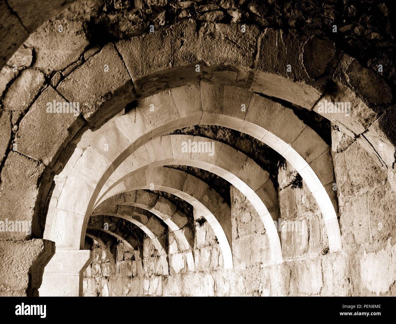 Hintereinander gebaute Rundbögen einer Ruine in Sepia - Stock Image