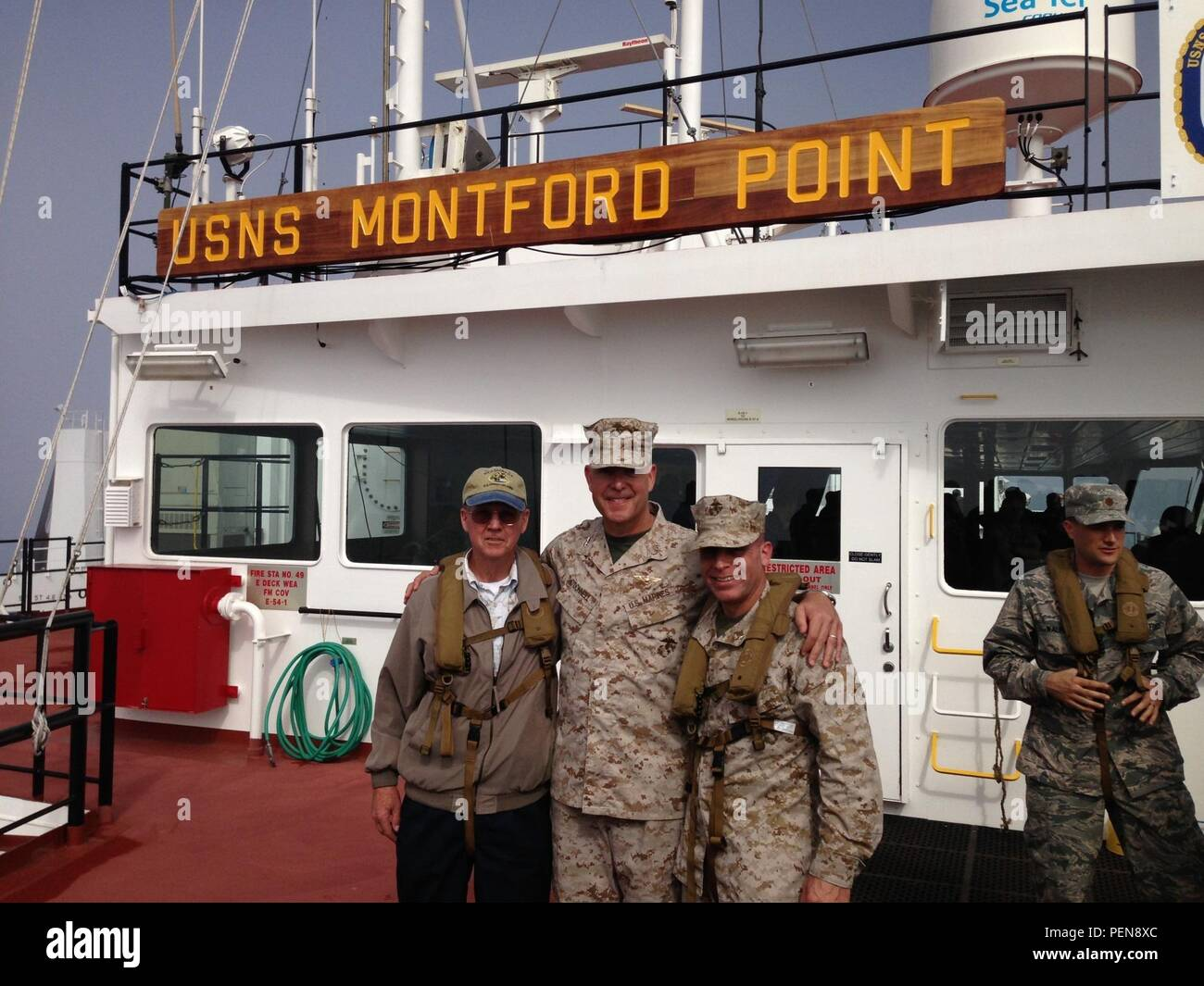 Jim Strock, Maj. Gen. Andrew W. O'Donnell, Jr. and Brig. Gen. Joaquin F. Malavet onboard 'USNS Montford Point,' the lead ship in a class of Mobile Landing Platforms which will be crucial to the seabasing initiative, in Sept. 2014. (Photo courtesy of James Strock) - Stock Image