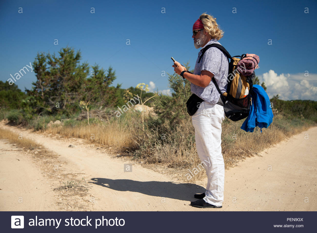 Traveler consults his mobile phone at a crossroads in a rural landscape - Stock Image