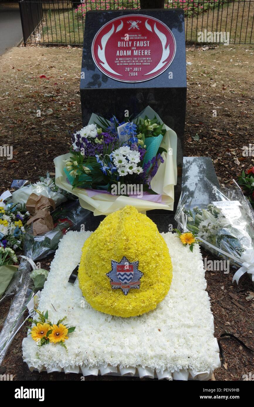 Bethnal Green park east London memorial to fire crew killed June 20 2004  with floral tribute helmet on the anniversary - Stock Image