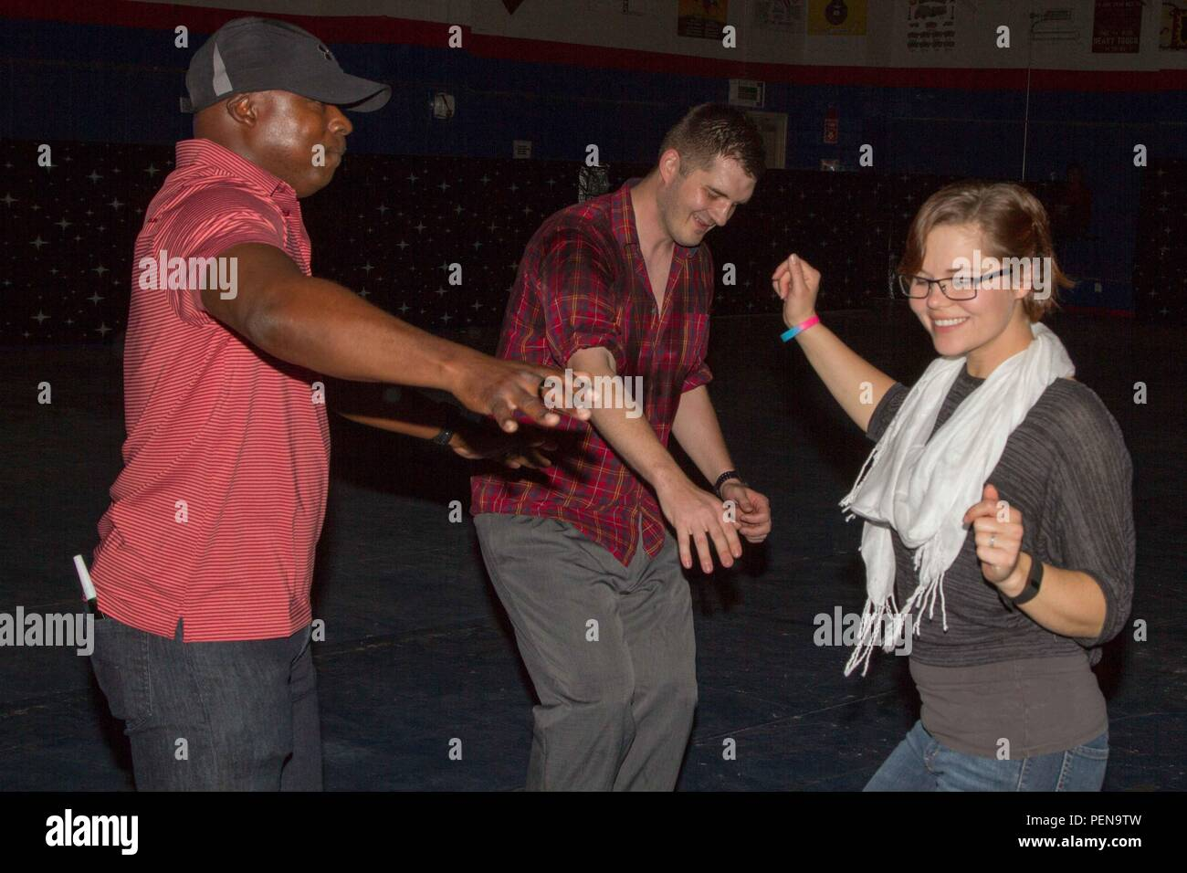 (from left to right) Capt. Marland Gibbert, Spc. Glenn Hahn and Sgt. Jessica Brown dance at the New Year's Eve party on Camp Arifjan, Kuwait, Dec. 31. During the event, service members danced to 1990s music, socialized and had refreshments before counting down to 2016 with a New Year's ball drop. (U.S. Army photo by Sgt. David N. Beckstrom, 19th Public Affairs Detachment, U.S. Army Central) - Stock Image