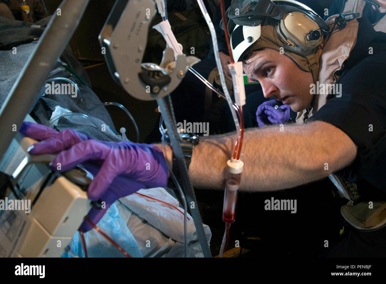 151231-N-AX638-107 ARABIAN GULF (Dec. 31, 2015) Hospital Corpsman 2nd Class Tracey Farris, from Arvin, Calif., an intensive care corpsman aboard USS Kearsarge attached to Fleet Surgical Team (FST) 4, monitors a patient's vital signs during a medical evacuation drill in an MV-22 Osprey. Kearsarge is the flagship for the Kearsarge Amphibious Ready Group (ARG) and, with the embarked 26th Marine Expeditionary Unit (MEU), is deployed in support of maritime security operations and theater security cooperation efforts in the U.S. 5th Fleet area of operations. (U.S. Navy photo by Mass Communication Sp - Stock Image